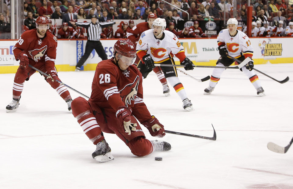 Photo - Phoenix Coyotes' Michael Stone (26) stops a pass as Calgary Flames' Ben Hanowski (58) and Lance Bouma (17) look on during the first period of an NHL hockey game on Saturday, March 15, 2014, in Glendale, Ariz. Coyotes' Chris Summers watches the action. (AP Photo/Matt York)