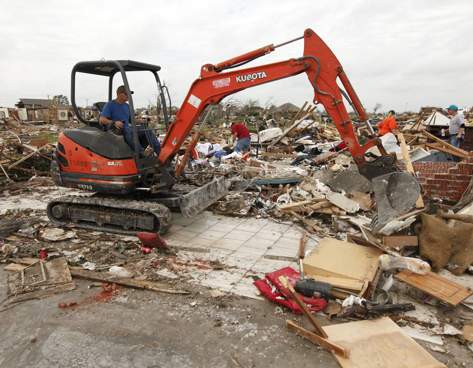 A small backhoe begins the process of removing the rubble of a home destroyed by the May 20th tornado near 145th and Robinson in Moore, OK, Saturday, May 25, 2013,  Photo by Paul Hellstern, The Oklahoman
