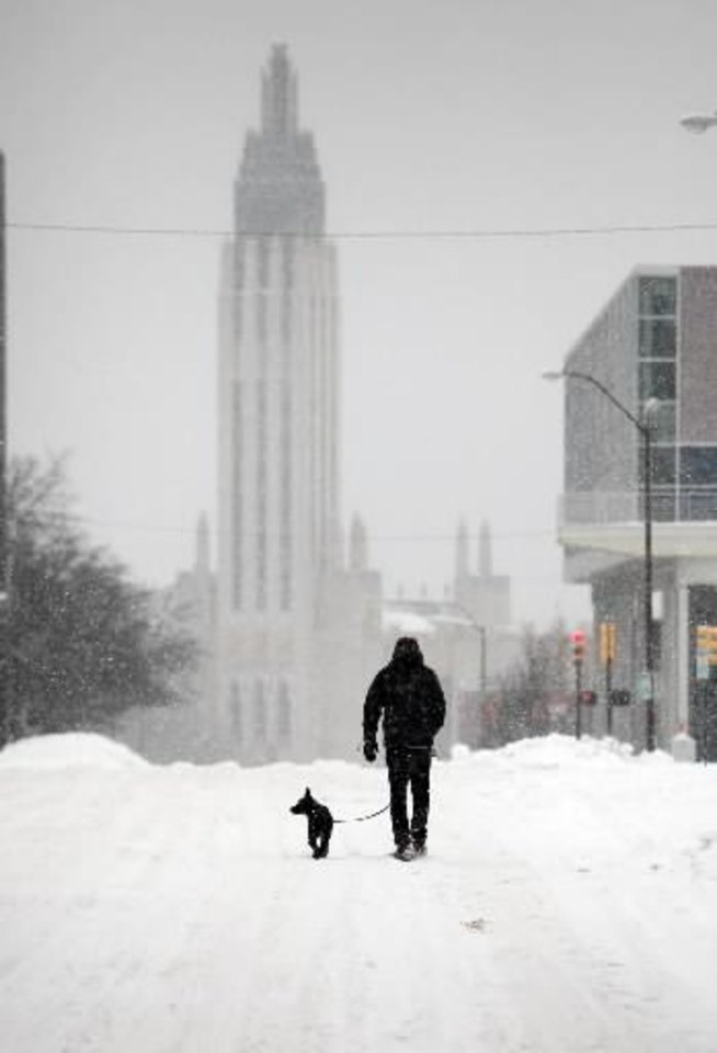 Photo - James Manning and his dog NASA walk down a snowy street in Tulsa, Okla on Friday, Feb. 4, 2011. Snow began falling again Friday on Oklahoma, just days after a blizzard that dumped up to 20 inches of snow, ice and sleet on the state shut down roads and closed schools across the state. (AP Photo/ Tulsa World, Stephen Pingry)