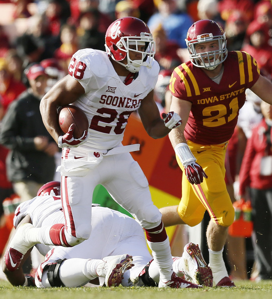 Photo - Oklahoma's Alex Ross (28) carries the ball away from Iowa State's Luke Knott (21) in the first quarter during a college football game between the University of Oklahoma Sooners (OU) and the Iowa State Cyclones (ISU) at Jack Trice Stadium in Ames, Iowa, Saturday, Nov. 1, 2014. Photo by Nate Billings, The Oklahoman