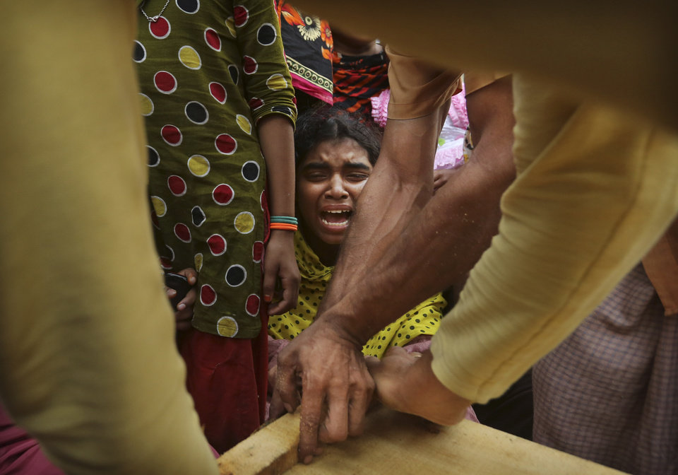 Photo - A Bangladeshi relative of garment worker Mohammed Abdullah cries as his coffin is nailed shut after collecting his body at a makeshift morgue in a schoolyard near a building that collapsed Wednesday in Savar, near Dhaka, Bangladesh, Saturday, April 27, 2013. Police in Bangladesh arrested two owners of a garment factory in a shoddily-constructed building that collapsed this week, killing hundreds of people, as protests spread to a second city Saturday with hundreds of people throwing stones and setting fire to vehicles. (AP Photo/Kevin Frayer)