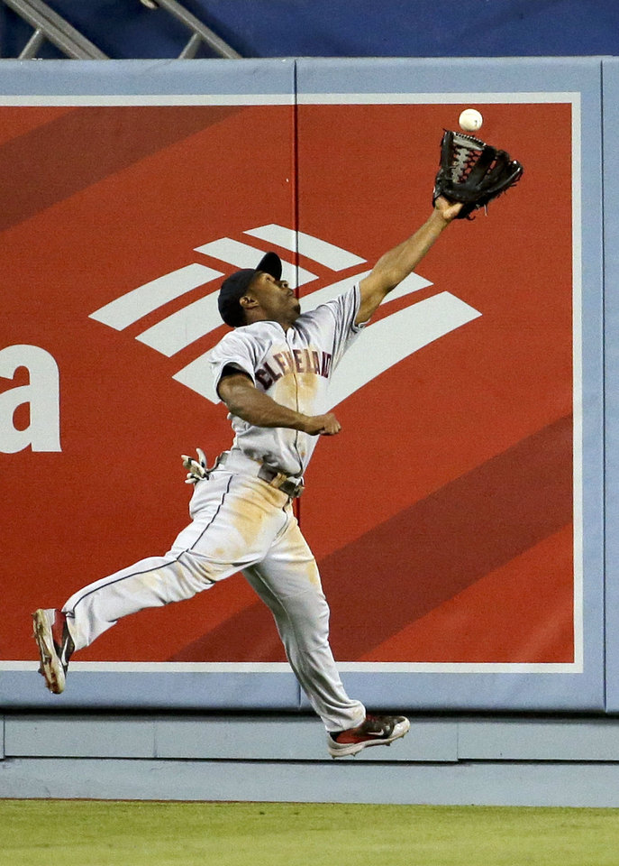 Photo - Cleveland Indians center fielder Michael Bourn can't get a glove on a double by Los Angeles Dodgers' Josh Beckett during the fourth inning of a baseball game in Los Angeles, Tuesday, July 1, 2014. (AP Photo/Chris Carlson)