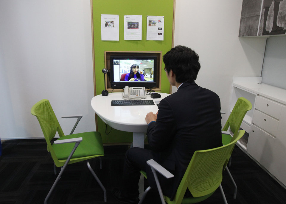 Photo - FILE - In this Friday, Jan. 11, 2013 file photo, customer Chung Yong-min does banking through a screen monitor connected to a video conference with bank employee Oh Ji-young, located in another office, at a Smart Banking Center in Seoul, South Korea. In an age when checks can be deposited by smartphone and almost everyone retrieves cash from ATMs, the corner bank can seem a relic, with its paper deposit slips, marble countertops and human tellers behind glass partitions. (AP Photo/Ahn Young-joon)