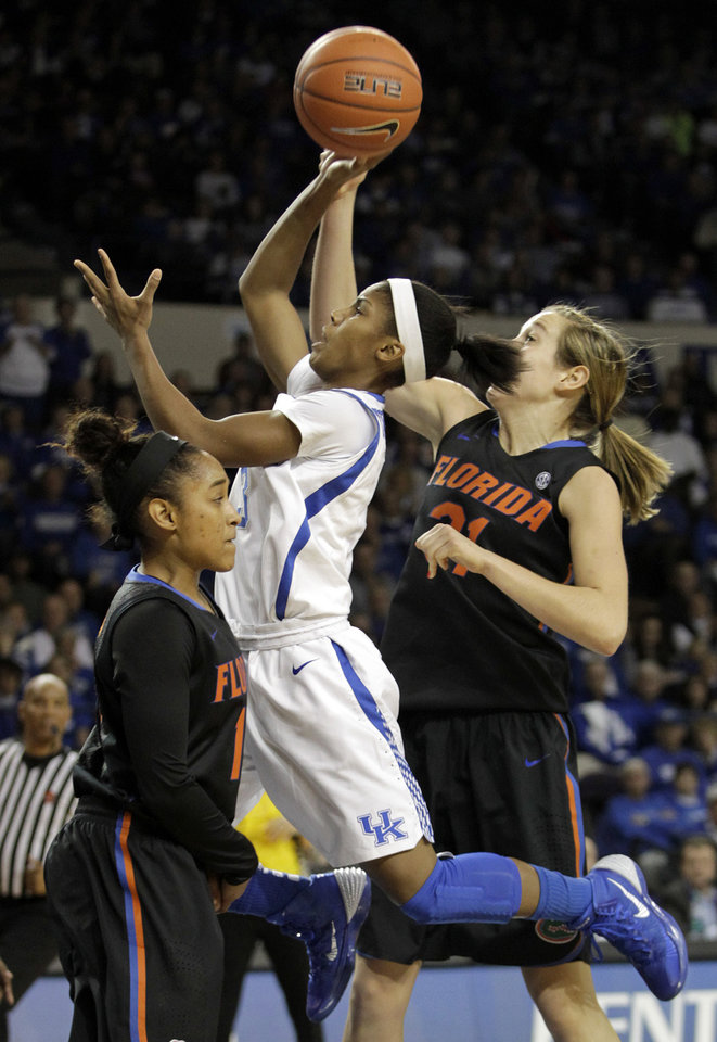 Photo - Kentucky's Janee Thompson, center, shoots between Florida's Cassie Peoples, left, and Lily Svete during the first half of an NCAA college basketball game, Sunday, Jan. 5, 2014, in Lexington, Ky. (AP Photo/James Crisp)