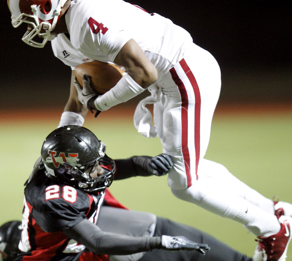 Owasso's Keon Hatcher is knocked off his feet by  Westmoore's Archie Ocloolee during their playoff game at Moore High School in Moore, Oklahoma, on Friday Nov. 19, 2010. Photo by John Clanton, The Oklahoman