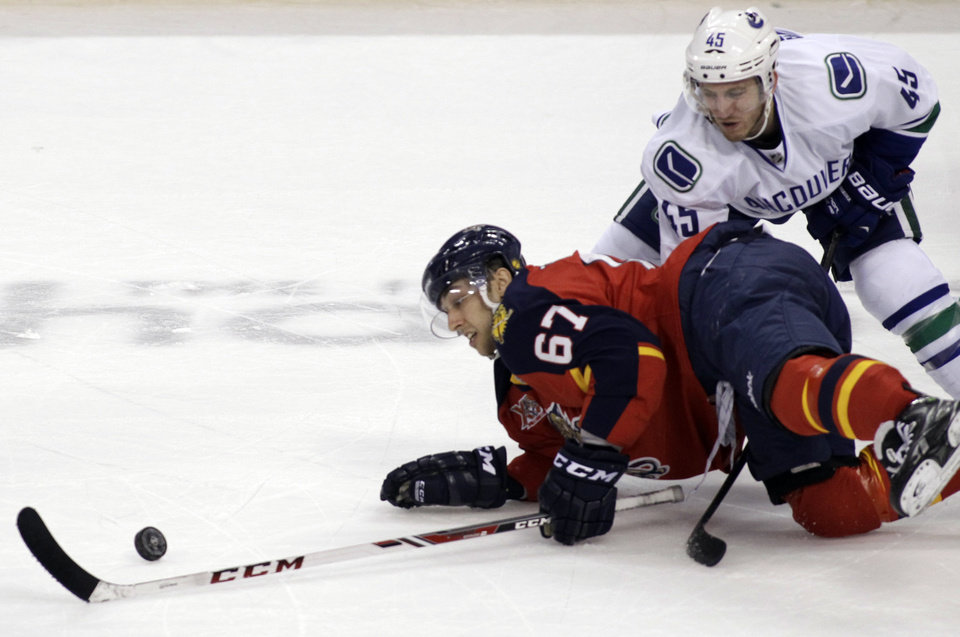 Photo - Florida Panthers' Vincent Trocheck (67) reaches for the puck as Vancouver Canucks' Jordan Schroeder (45) defends during the first period of an NHL hockey game on Sunday, March 16, 2014, in Sunrise, Fla. (AP Photo/Luis M. Alvarez)