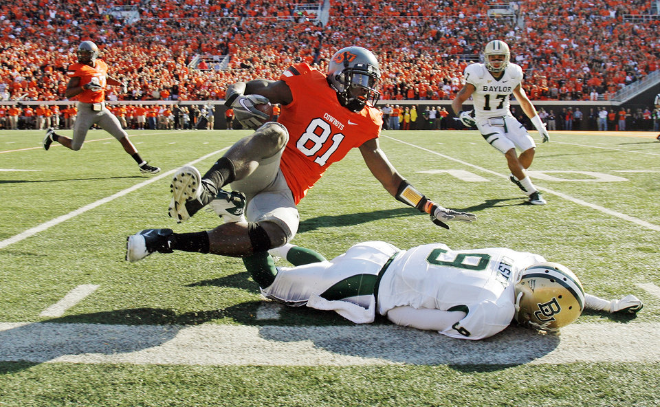 Photo - OSU's Justin Blackmon (81) collides with Baylor's Chance Casey (9) at the end of a long run after a catch in the second quarter during a college football game between the Oklahoma State University Cowboys (OSU) and the Baylor University Bears (BU) at Boone Pickens Stadium in Stillwater, Okla., Saturday, Oct. 29, 2011. Photo by Nate Billings, The Oklahoman