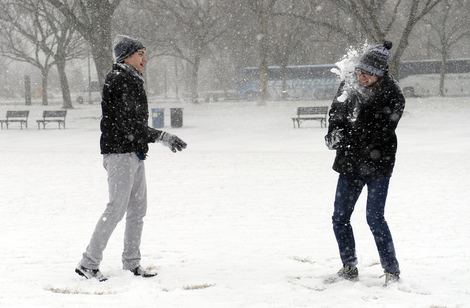 Photo - Rick Mendenhall of Albuquerque, N.M., right, gets hit in the face during a snowball fight with his friend Jeff Scott of Los Angeles, left, on the National Mall in Washington during the start of a major snowstorm, Tuesday, Jan. 21, 2014. Many government offices and schools closed before the first flake of snow, but there were signs Tuesday that significant winter weather was moving into the mid-Atlantic region as heavy snow began falling.(AP Photo/Susan Walsh)