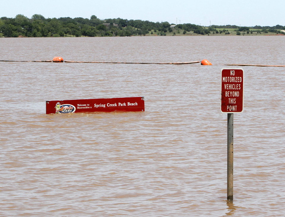 Photo - The swimming beach at Spring Creek Park at Arcadia Lake is submerged in floodwaters after Friday's storms. PHOTO BY PAUL HELLSTERN, THE OKLAHOMAN.  PAUL HELLSTERN - OKLAHOMAN