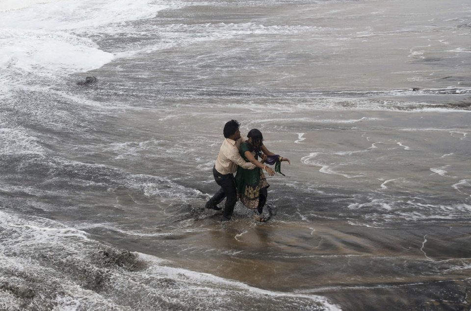 Photo - A man, left rescues a woman who fell in water due to strong tidal waves prior to a cyclone on the Bay of Bengal coast at Gopalpur, Orissa, about 285 kilometers (178 miles) north east of Visakhapatnam, India, Sunday, Oct. 12, 2014. Trees were uprooted and power cables snapped as a powerful cyclone swept through the Bay of Bengal and slammed into the southern city of Visakhapatnam, one of two storms pounding Asia on Sunday. (AP Photo/Biswaranjan Rout)