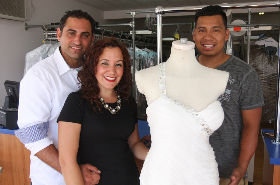 Photo - In this July 28, 2014 photo,  Michael, left, and Nicole Pagliaro pose with her wedding dress at the South Beach Dry Cleaners with owner Hector Pacheco in the Staten Island borough of New York where Nicole Pagliaro discovered the shop displaying her dress long after assuming it had been lost to Superstorm Sandy. The shop she brought it to for cleaning was destroyed by the storm, but two weeks ago Pagliaro took a different route to work and spotted it in the window of the dry cleaner's new store. (AP Photo/Staten Island Advance, Hilton Flores)
