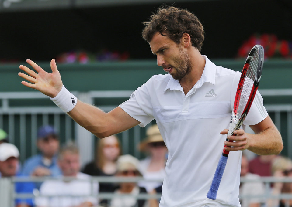 Photo - Ernests Gulbis of Latvia gestures during to Sergiy Stakhovsky of Ukraine during their men's singles match at the All England Lawn Tennis Championships in Wimbledon, London,  Wednesday, June  25, 2014. (AP Photo/Ben Curtis)