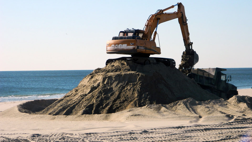 Photo - In this April 23, 2014 photo, a grane sits on top of a giant pile of sand that needs to be redistributed on the newly replenished Spring Lake N.J., beach. Experts say most of the Jersey shore's beaches came through the winter in fine shape, and are in their best condition in years as the second summer after Superstorm Sandy approaches. (AP Photo/Wayne Parry)