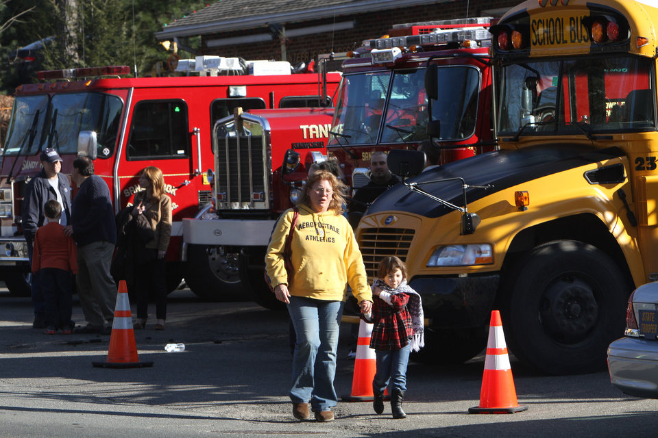 Photo - CORRECTS LOCATION TO FIREHOUSE - Parents walk away  after being reunited at the Sandy Hook firehouse following a mass shooting at the Sandy Hook Elementary School, Friday, Dec. 14, 2012 in Newtown, Conn. with their children following a shooting at the school, Friday, Dec. 14, 2012 in Newtown, Conn.  (AP Photo/The Journal News, Frank Becerra Jr.) MANDATORY CREDIT, NYC OUT, NO SALES, TV OUT, NEWSDAY OUT; MAGS OUT
