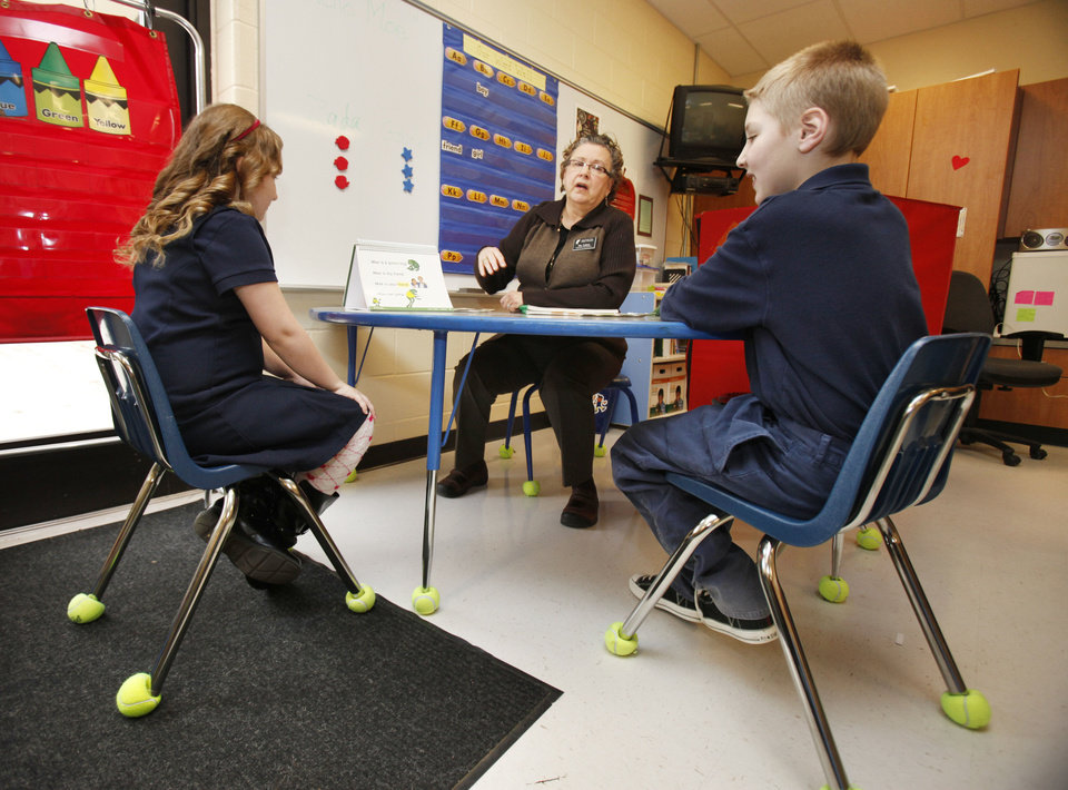 Photo - Special Education teacher Linda Felton works with 7 year old Zada Lamb and eight year old Gabriel Brown during a class for autistic children at Sequoyah Elementary School in Oklahoma City, OK, Thursday, Feb. 9, 2012. By Paul Hellstern, The Oklahoman