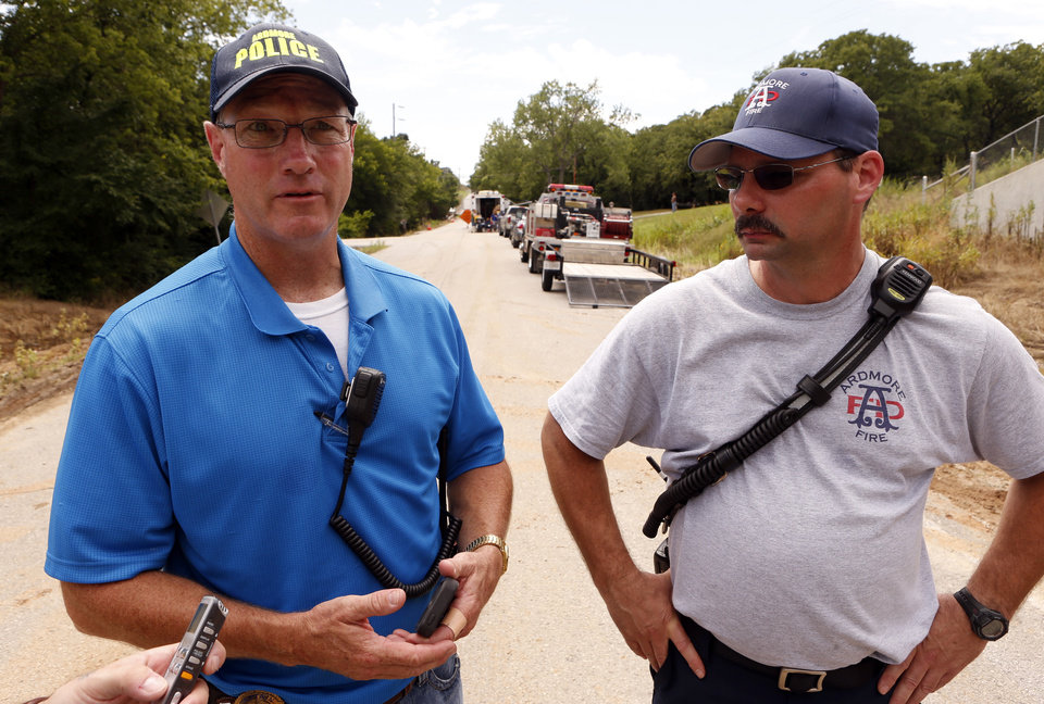 Photo - Police Capt. Eric Hamblin and Shift Commander Scott Richards report the recovery of the body of two-year-old Jeremiah Mayer from a creek bed behind them on Thursday, June 18, 2015 in Ardmore, Okla. Photo by Steve Sisney, The Oklahoman
