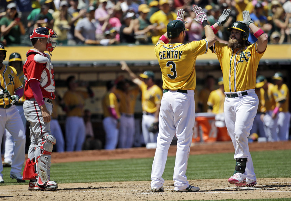 Photo - Oakland Athletics' Derek Norris, right, celebrates his second three-run home run of a baseball game with teammate Craig Gentry (3) as Washington Nationals catcher Jose Lobaton, left, watches during the second inning on Sunday, May 11, 2014, in Oakland, Calif. (AP Photo/Marcio Jose Sanchez)