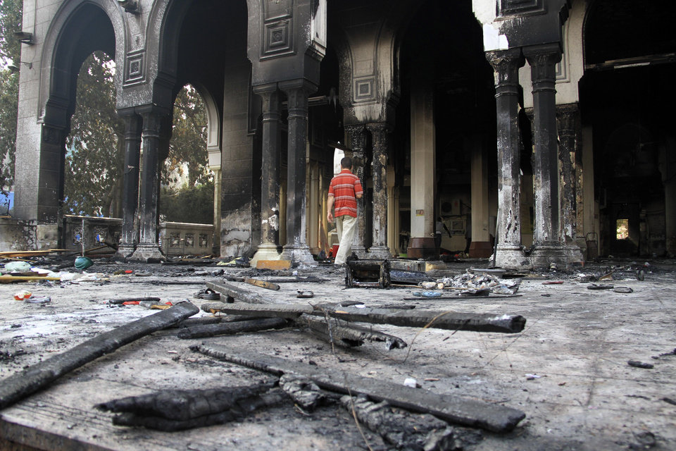 Photo - Egyptians walk among the burned remains of the Rabaah al-Adawiya mosque, in the center of the largest protest  camp of supporters of ousted President Mohammed Morsi, that was cleared by security forces, in the district of Nasr City, Cairo, Egypt, Thursday, Aug. 15, 2013. The death toll keeps going up in Egypt after security forces swept through two sit-in sites yesterday, operated by supporters of former President Mohammed Morsi. An Egyptian Health Ministry spokesman now says over 400 people died in the violence that has prompted international criticism. (AP Photo/Ahmed Gomaa)