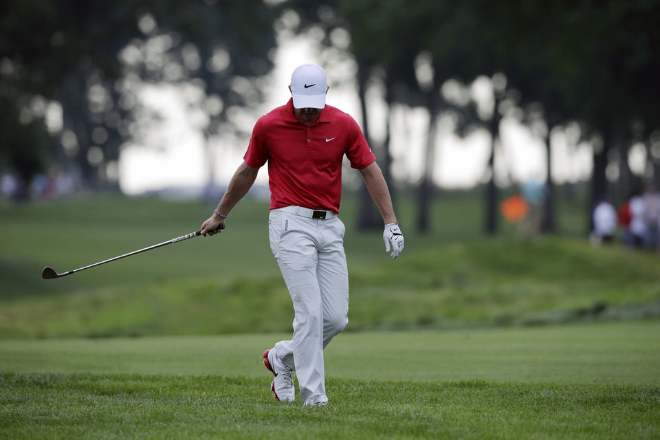 Photo - Rory McIlroy, of Northern Ireland, reacts to hitting into a sand trap on the 13th hole during the first round of play at The Barclays golf tournament Thursday, Aug. 21, 2014, in Paramus, N.J.  (AP Photo/Mel Evans)