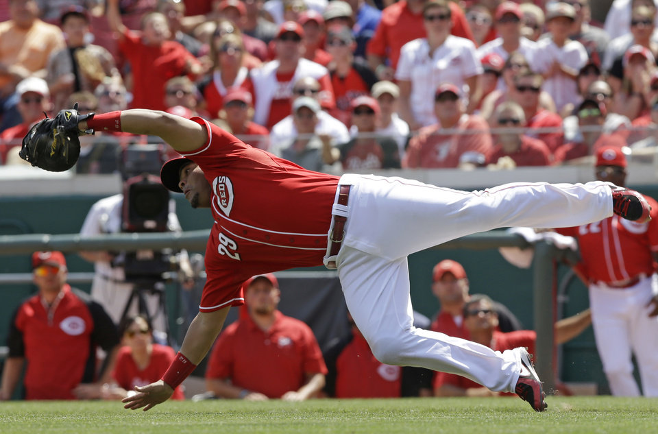 Photo - Cincinnati Reds first baseman Brayan Pena makes a diving catch on a pop fly hit by Chicago Cubs' Justin Ruggiano with the bases loaded in the 10th inning of a baseball game, Thursday, July 10, 2014, in Cincinnati. Chicago won 6-4 in 12 innings. (AP Photo/Al Behrman)