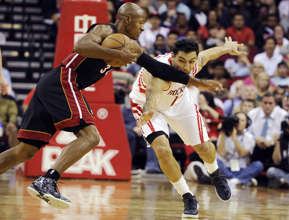 Miami Heat's Ray Allen (34) keeps Houston Rockets' Carlos Delfino (10) away from the ball in the second half of an NBA basketball game, Monday, Nov. 12, 2012, in Houston. The Heat won 113-110. (AP Photo/Pat Sullivan)