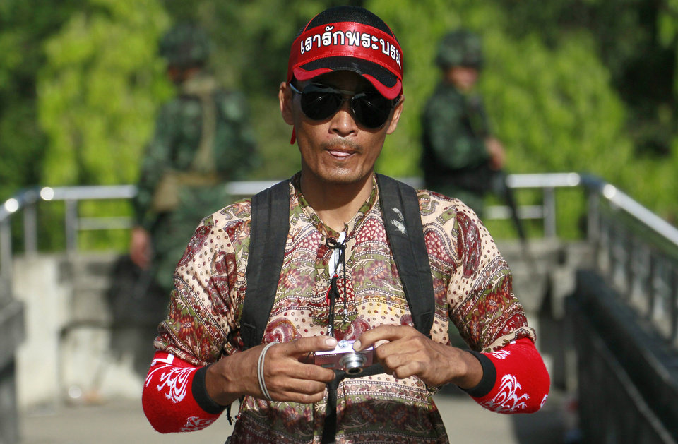 Photo - A pro-government or Red Shirt protester walks near the pro-government rally site on the outskirts of Bangkok, Thailand Tuesday, May 20, 2014. Thailand's army declared martial law before dawn Tuesday in a surprise announcement it said was aimed at keeping the country stable after six months of sometimes violent political unrest. The military, however, denied a coup d'etat was underway. (AP Photo/Wason Wanichakorn)