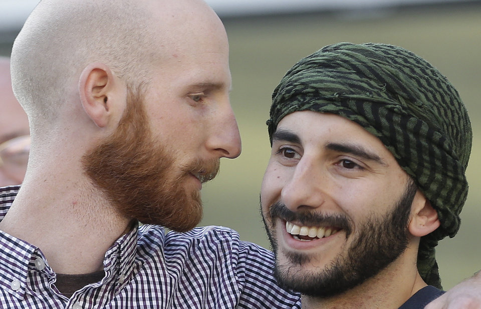 Photo - In this Monday, April 7, 2014 photo, plaintiffs Derek Kitchen, left, and Moudi Sbeity stand together during the Utah Unites for Marriage