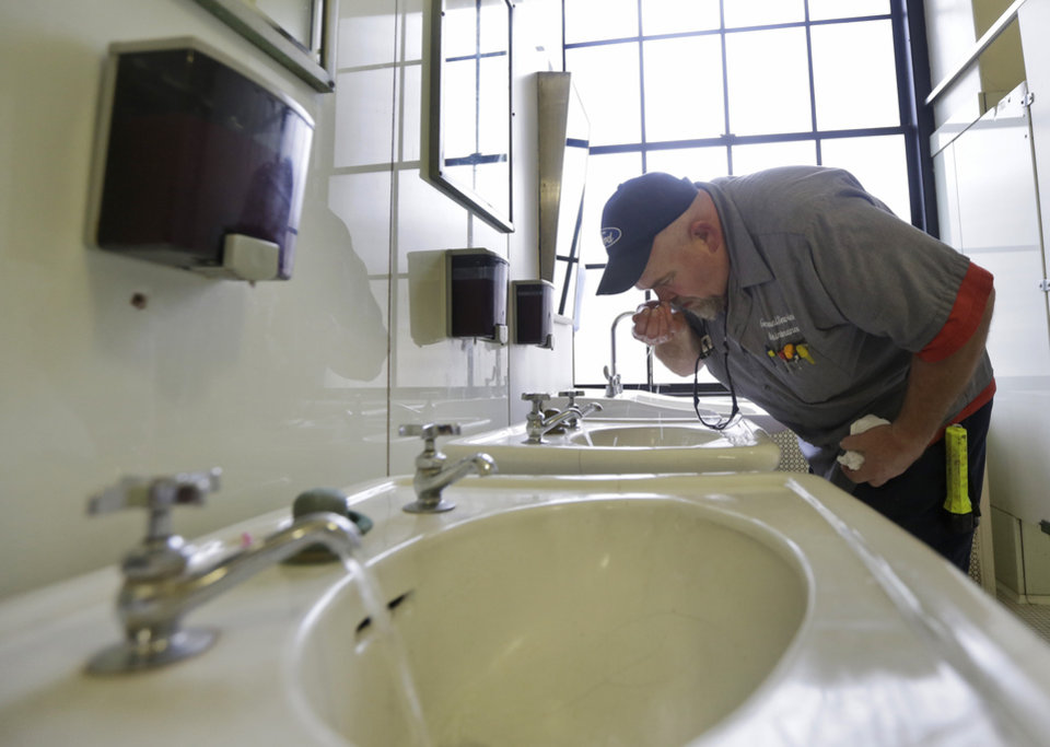 Photo - CORRECTS STATE TO W.VA. INSTEAD OF VA. - Al Jones of the West Virginia department of General Services tests the water as he flushes the faucet and opens a rest room on the first floor of the State Capitol in Charleston, W.Va., Monday, Jan. 13, 2014.  Gov. Earl Tomblin announced that the water system is ready to be flushed by zones with safe drinking water after the chemical spill on Jan. 9. It could still be several days before everyone is cleared to use the water again, but officials were grateful to give the green light to about 6,000 to 10,000 customers. (AP Photo/Steve Helber)
