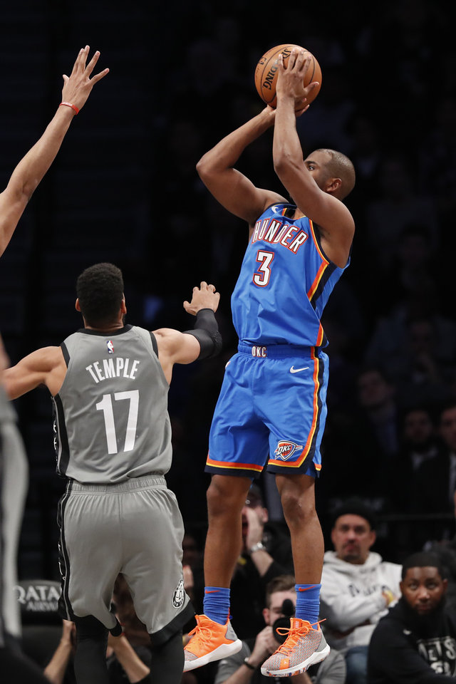 Photo - Oklahoma City Thunder guard Chris Paul (3) shoots for three points with Brooklyn Nets guard Garrett Temple (17) defending during overtime of an NBA basketball game, Tuesday, Jan. 7, 2020, in New York. Paul has 28 points to help the Thunder defeat the Nets 111-103 in overtime. (AP Photo/Kathy Willens)
