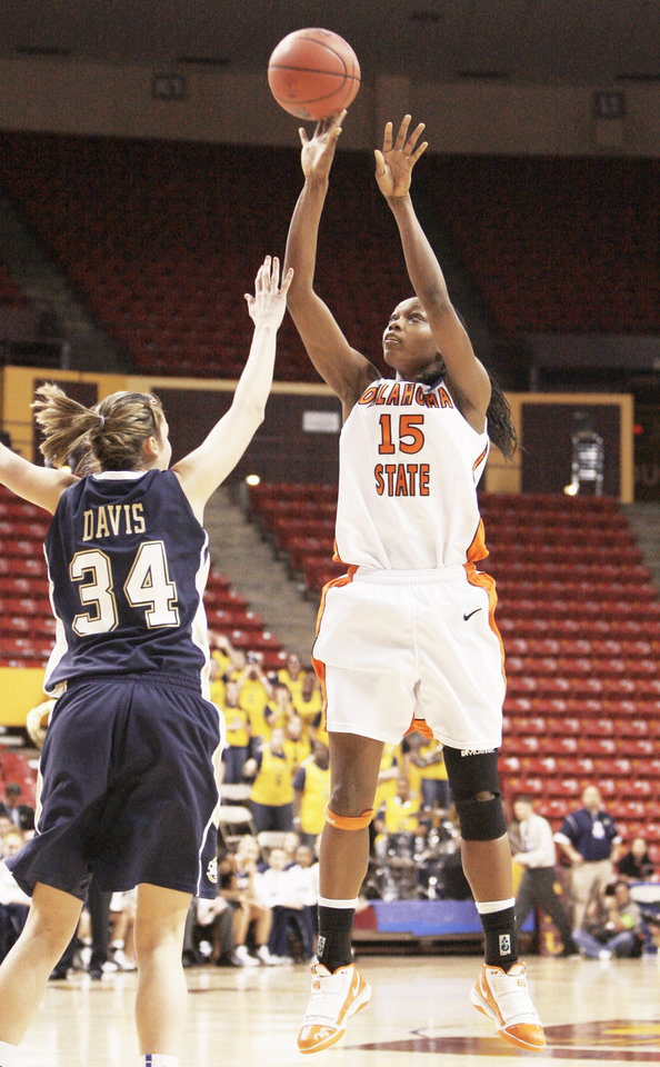 OSU's Toni Young, right, scores over Chattanooga's Michelle Davis during the Cowgirls' 70-63 first-round  win. AP photo