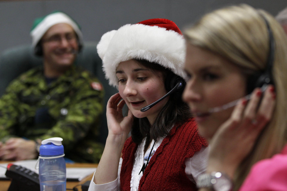 FILE - In this Dec. 24, 2012 file photo, volunteer Katherine Beaupre takes phone calls from children asking where Santa is and when he will deliver presents to their house,during the annual NORAD Tracks Santa Operation, at the North American Aerospace Defense Command, or NORAD, at Peterson Air Force Base, in Colorado Springs, Colo. The U.S. and Canadian military will entertain millions of kids again this Christmas Eve with second-by-second updates on Santa�s global whereabouts. (AP Photo/Brennan Linsley, File)