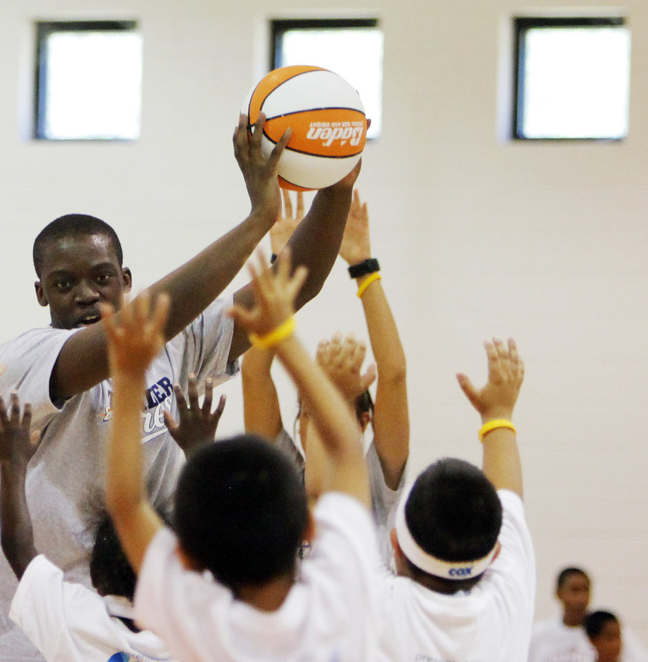 Photo - Oklahoma City Thunder draft pick Reggie Jackson works with children during a Thunder Youth Basketball Camp at the Boys and Girls Club of Oklahoma County in Oklahoma City, Saturday, June 25, 2011. The Thunder selected Reggie Jackson with the 24th pick in this year's NBA draft. Photo by Nate Billings, The Oklahoman