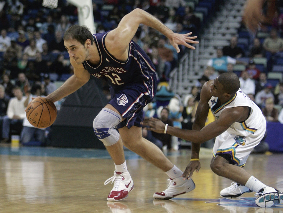 Photo - New Jersey Nets center Nenad Krstic (12), of Serbia,  is grabbed by New Orleans Hornets Chris Paul (3) in the first half of their NBA basketball game in New Orleans, Friday, March 7, 2008. Paul was called for a foul on the play. (AP Photo/Bill Haber) ORG XMIT: LAWH105