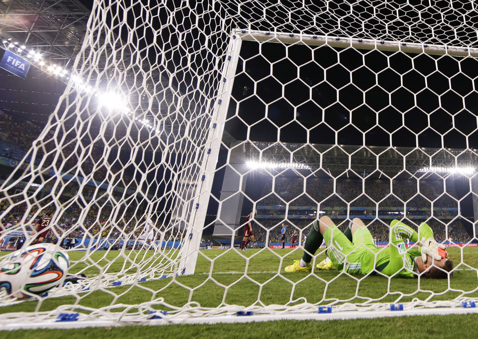 Photo - Russia's goalkeeper Igor Akinfeev covers his face after dropping the ball as South Korea's Lee Keun-ho scores the opening goal during the group H World Cup soccer match between Russia and South Korea at the Arena Pantanal in Cuiaba, Brazil, Tuesday, June 17, 2014.  (AP Photo/Lee Jin-Man)