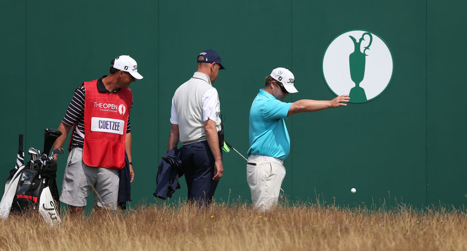 Photo - George Coetzee of South Africa is watched by his caddie and a member of the rules committee as he takes a drop shot on the 18th during the second day of the British Open Golf championship at the Royal Liverpool golf club, Hoylake, England, Friday July 18, 2014. (AP Photo/Jon Super)