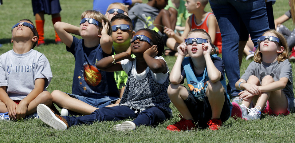 Photo - Students at Washington Irving Elementary School watch the eclipse in Edmond, Monday August 21, 2017. Students, parents and teachers viewed the eclipse on the playground. Photo By Steve Gooch, The Oklahoman