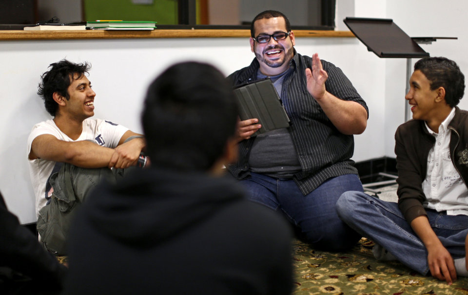 Photo - Abdur-Rahman Taleb, center, the new youth director for the Islamic Society of Greater Oklahoma City, leads an Islamic studies discussion as part of youth activities at the Mercy School complex, 14001 N Harvey. The youths include Rafeh Waheed, 17, at left, and Mohamed Khaled, 13.   BRYAN TERRY - THE OKLAHOMAN