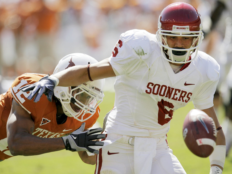 Photo - OU's Cameron Kenney (6) fumbles the ball as he tries to avoid Earl Thomas (12) of Texas in the second quarter during the Red River Rivalry college football game between the University of Oklahoma Sooners (OU) and the University of Texas Longhorns (UT) at the Cotton Bowl in Dallas, Texas, Saturday, Oct. 17, 2009. OU recovered the fumble. Photo by Nate Billings, The Oklahoman