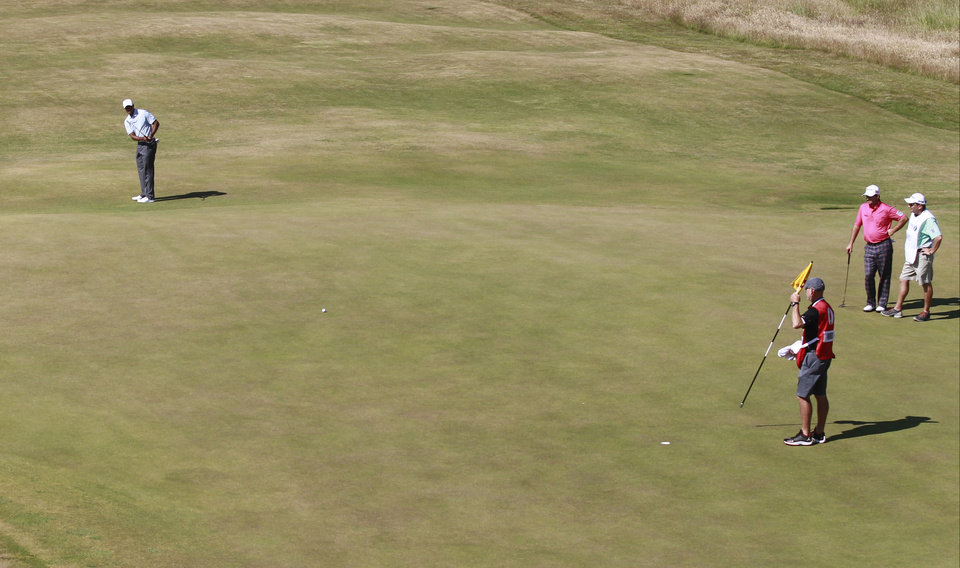 Photo - Tiger Woods of the United States putts on the 5th green during the second round of the British Open Golf Championship at Muirfield, Scotland, Friday July 19, 2013. (AP Photo/Peter Morrison)