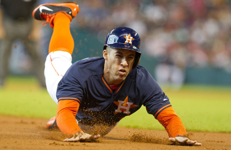 Photo - George Springer, of the Houston Astros, steals third base during the first inning of a baseball game in Houston Sunday, June 29, 2014. Springer scored on the next play off Jesus Guzman's RBI single to left field. (AP Photo/ The Courier, Jason Fochtman)