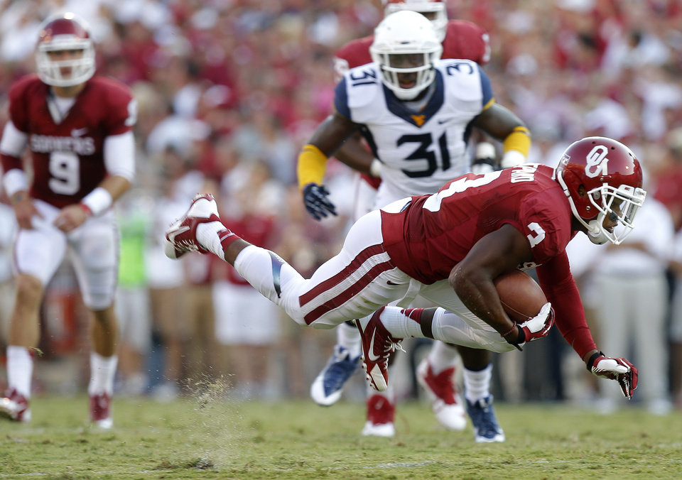 Photo - Oklahoma's Sterling Shepard (3) gets tripped up during a college football game between the University of Oklahoma Sooners (OU) and the West Virginia University Mountaineers at Gaylord Family-Oklahoma Memorial Stadium in Norman, Okla., on Saturday, Sept. 7, 2013. Photo by Bryan Terry, The Oklahoman