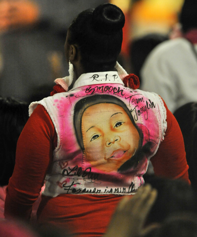 Photo - A mourner pays tribute to 6-month old Jonylah Watkins during her funeral at New Beginnings Church in Chicago, Tuesday, March, 19, 2013. Jonylah was killed when a gunman fired at a minivan as she sat on her father's lap on March 11. (AP Photo/Paul Beaty)