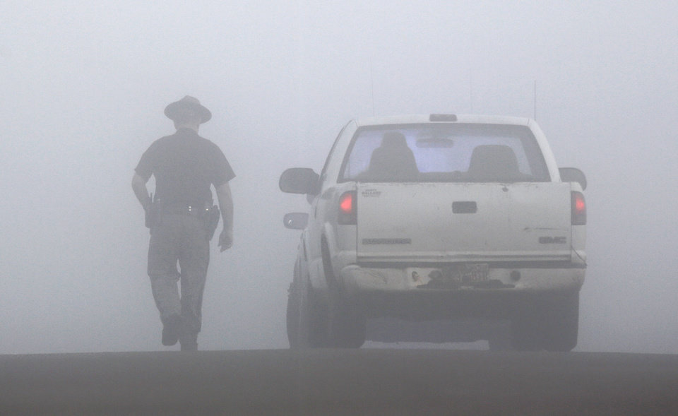 Photo - An Oklahoma Highway Patrol trooper returns to his patrol car after talking to a motorist in heavy fog on a county road about 10 miles north of Butler Monday morning, Oct. 31, 2016. The trooper is controlling access to scene where double murder suspect Michael Vance, Jr. was killed Sunday night in a gun battle with law officers. Photo by Jim Beckel, The Oklahoman