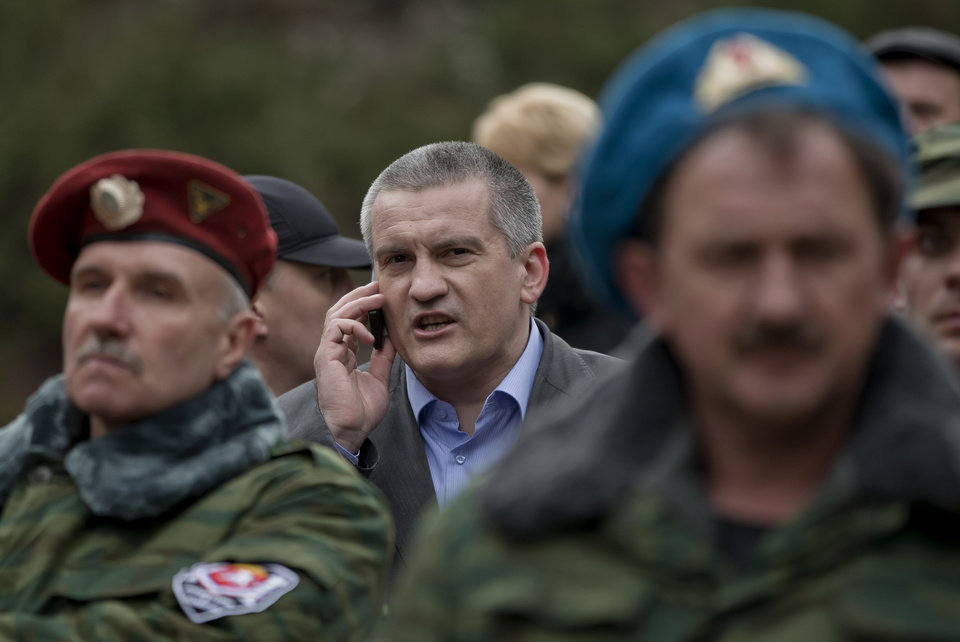 Photo - FILE - In this Saturday, March 8, 2014 file photo, Crimean Premier Sergei Aksyonov, center, speaks on a mobile phone as he attends the swearing in ceremony for the first unit of a pro-Russian armed force, dubbed the