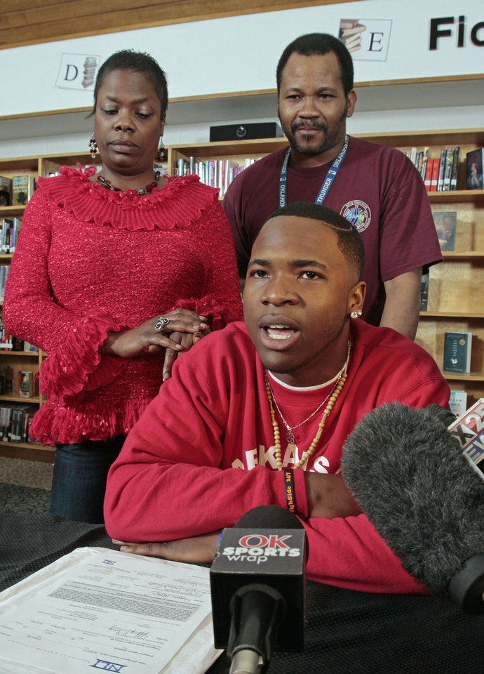 Norman High school player Donovan Roberts, backed by his parents, Katrice Roberts Powell and Londell Roberts, signs a letter of intent to play for Arkansas on Wednesday, Feb. 1, 2012, in Norman, Okla.   Photo by Steve Sisney, The Oklahoman