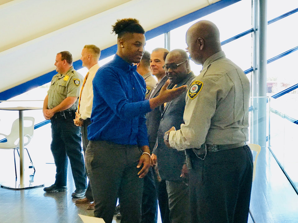 Photo -  Damian Byest, of Moore, thanks Oklahoma City police Sgt. Justin Echols, at a recent graduation for the police department's Juvenile Intervention Program held at the Devon Boathouse. [Photo by Carla Hinton, The Oklahoman]