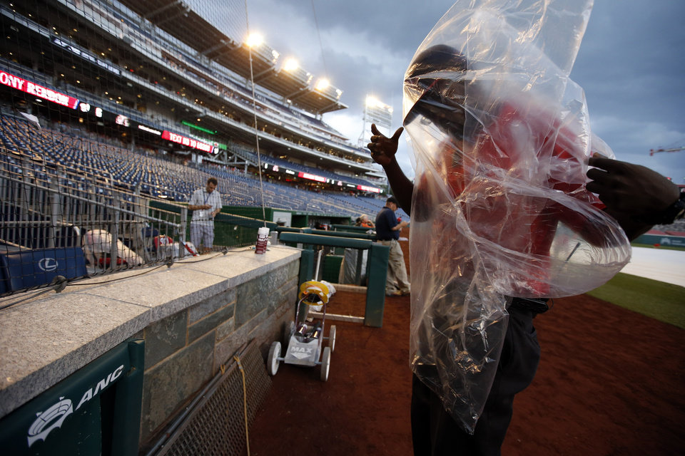Photo - Field security officer Sam Richards works to put on his poncho as the wind picks up during a rain delayed start of an interleague baseball game between the Washington Nationals and the Baltimore Orioles at Nationals Park, Tuesday, July 8, 2014, in Washington. (AP Photo/Alex Brandon)