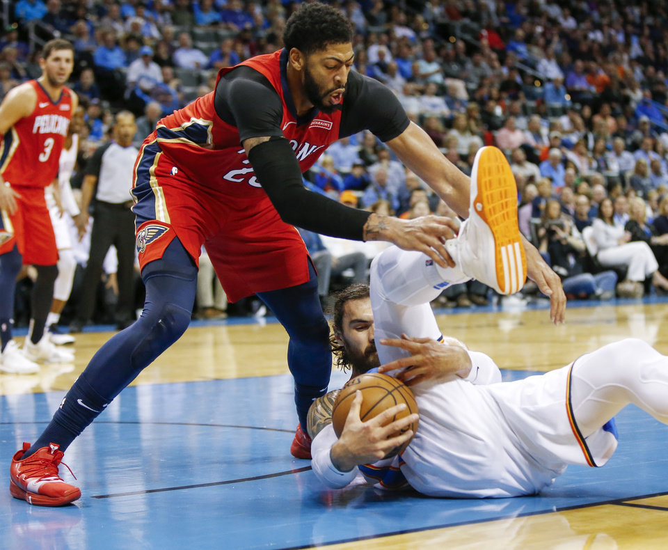 Photo - Oklahoma City's Steven Adams (12) grabs a loose ball in front of New Orleans' Anthony Davis (23) during an NBA basketball game between the Oklahoma City Thunder and the New Orleans Pelicans at Chesapeake Energy Arena in Oklahoma City, Monday, Nov. 5, 2018. Photo by Nate Billings, The Oklahoman