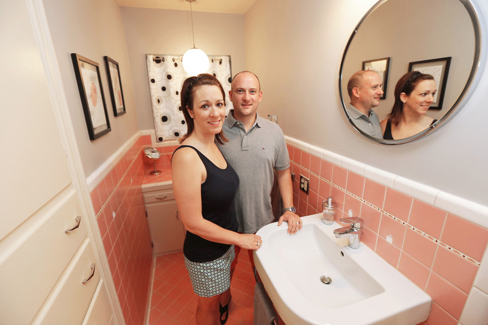 Photo - Lindsey and Mike  Deatsch show one of the two pink bathrooms they saved in their 1949 home on Venice Boulevard in Oklahoma City.   Steve Gooch - The Oklahoman