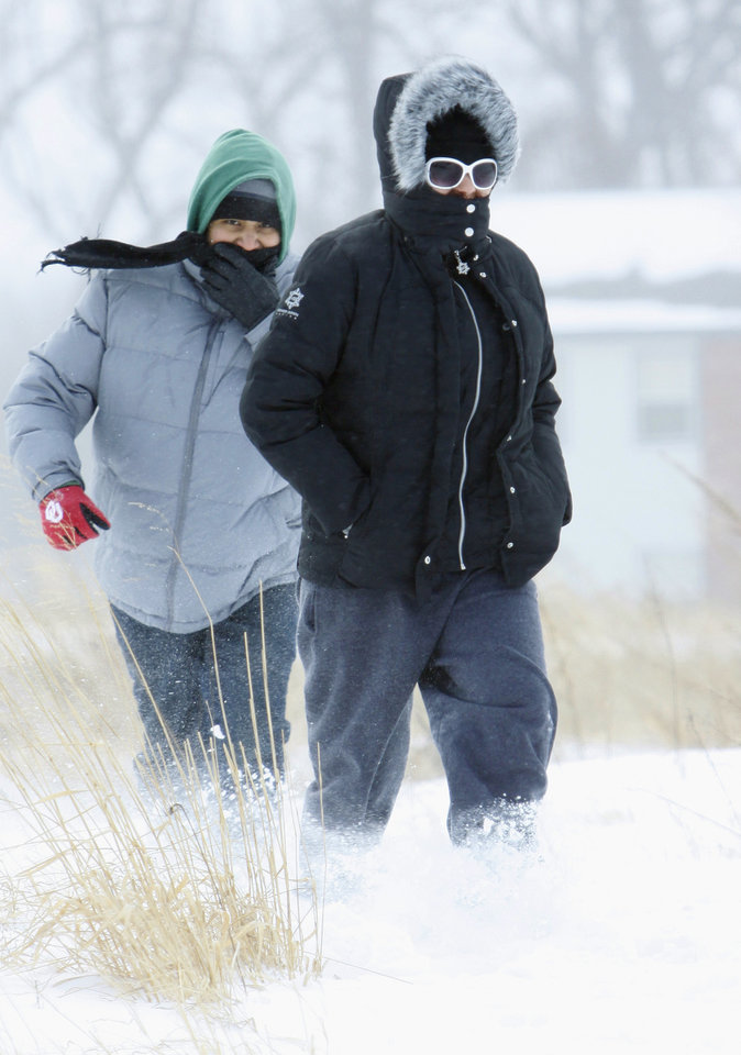 Photo - Isaac Parton and Rachele Tsoodle walk near Highway 9 and SW 24th Ave early in the afternoon after an epic winter storm on Tuesday, February 1, 2011, in Norman, Okla.  Photo by Steve Sisney, The Oklahoman